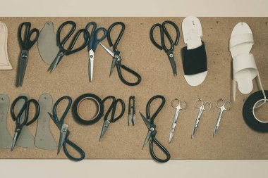top view of various tools and scissors at shoemaker workshop