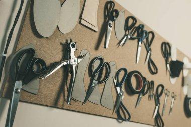 Various scissors hanging on board at shoemaker workshop stock vector