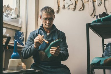 mature shoemaker holding boot workpiece and working with sole at his traditional workshop