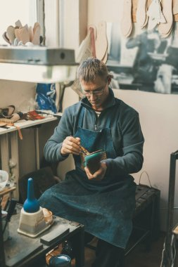 mature cobbler holding boot workpiece and working with sole while sitting at at his traditional workshop