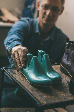 selective focus of shoemaker holding footwear workpieces from shelf in workshop