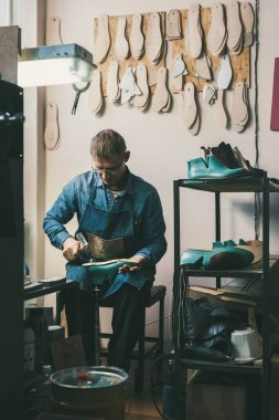 mature shoemaker working with footwear workpieces at workshop