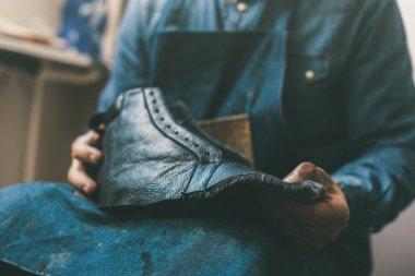 cropped shot of cobbler holding unfinished leather shoe at workshop