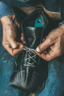 cropped shot of shoemaker lacing up unfinished leather boot
