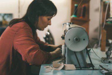 side view of seamstress working with sewing machine and leather at shoemaker workshop