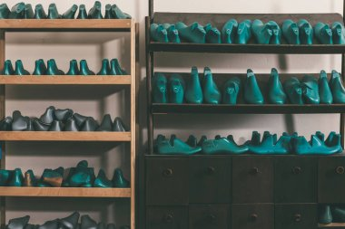 plastic footwear workpieces on shelves at cobbler shop