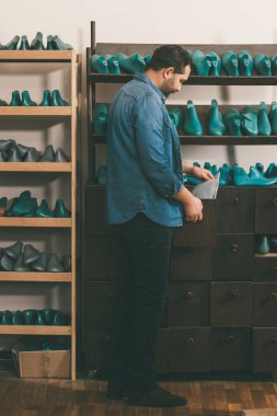 side view of shoemaker holding papers while working with footwear workpieces at workshop