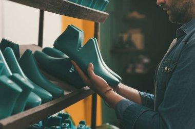 cropped shot of bearded shoemaker holding footwear workpieces