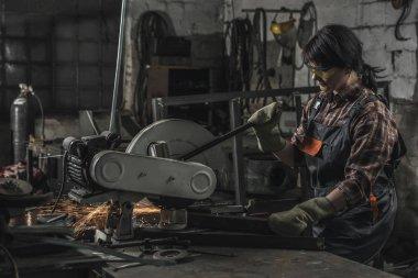 Female welder in protective googles using welding torch in workshop stock vector