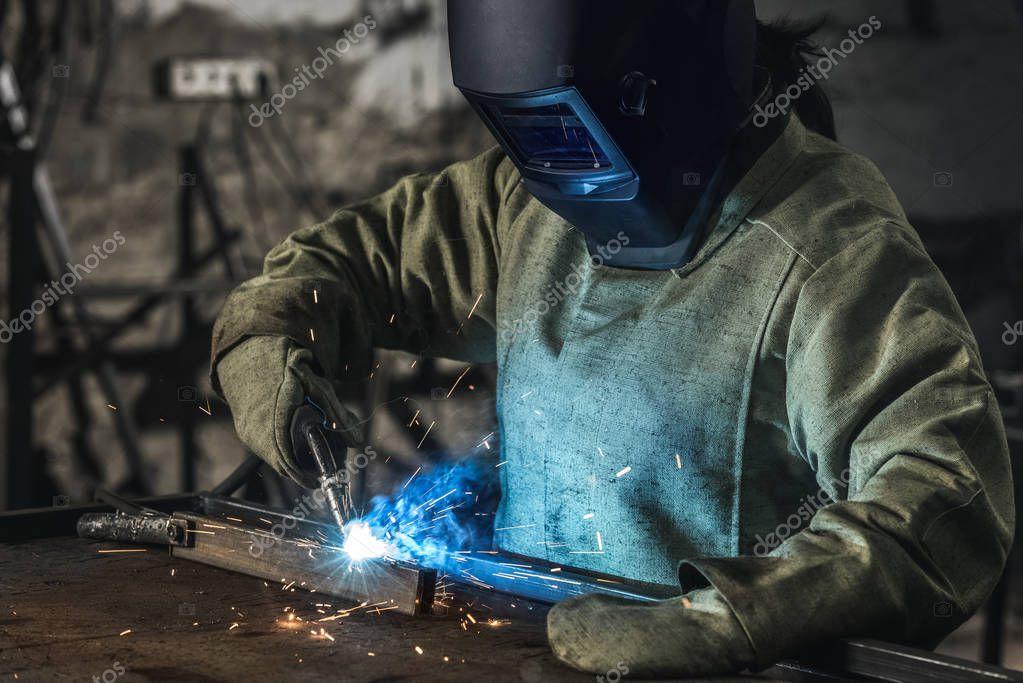 Manual worker in protective helmet with welding torch working in workshop stock vector