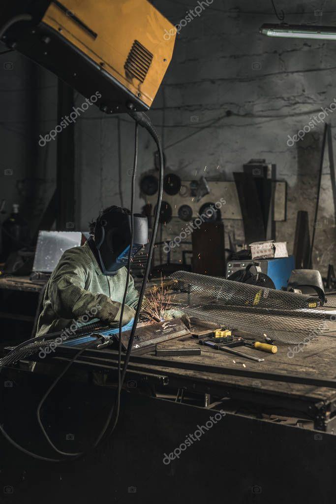 Side view of welder in protective work wear working with welding torch in workshop stock vector