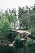 a gyönyörű fenyves erdőben sziklás sziklán nyugodt tóra