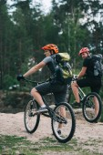 Fotografie active young trial bikers riding in forest on cloudy day