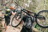 zadní pohled mladých zkušební motorkářů nošení kola na zádech v lese a jít do kopce