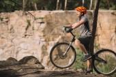 boční pohled pohledný mladý muž stojící s zkušební kolo v lese