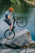 extrémní zkušební biker balancování na zadní kolo na skalnatém útesu nad jezerem
