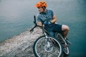 mladí zkušební biker odpočinkem na skalnatém útesu nad vodou a hledat dál