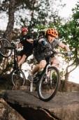 Fotografie mladí zkušební cyklisty jízda na skále v borovém lese