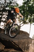 bottom view of extreme trial biker riding on rocks outdoors
