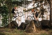 extreme trial bikers performing stunts on rocks outdoors