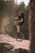 hezký pokus motorkář na zadní kolo na skalách venku