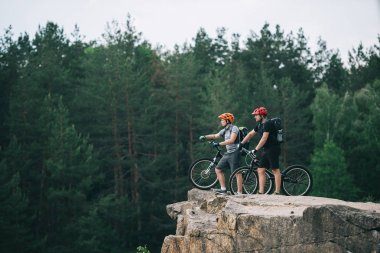 side view of young trial bikers standing on rocky cliff with blurred pine forest on background and pointing somewhere