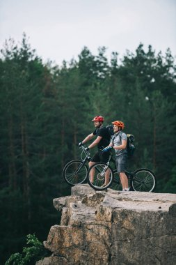 side view of happy young trial bikers standing on rocky cliff with blurred pine forest on background and looking away