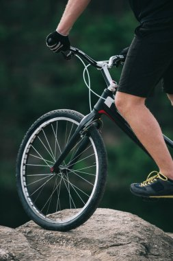 cropped shot of trial biker balancing on rock outdoors