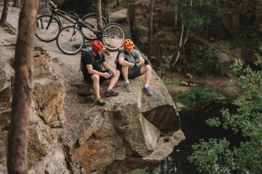 high angle view of active young trial bikers relaxing on rocky cliff after ride