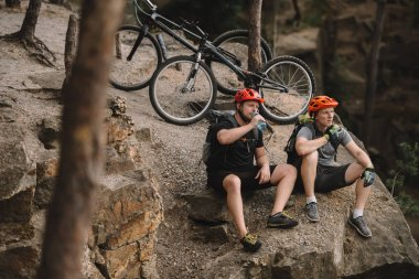 High angle view of young trial bikers relaxing on rocky cliff after ride and having meal stock vector