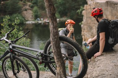 young trial bikers having rest on rocky cliff after ride