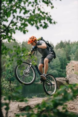 young trial biker performing stunt outdoors in front of forest lake