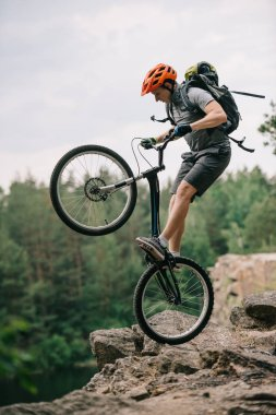 extreme trial biker standing on back wheel on rocky cliff
