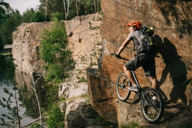 young trial biker with bicycle standing on cliff and looking at beautiful landscape