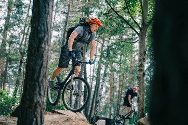 active young trial bikers riding at beautiful forest