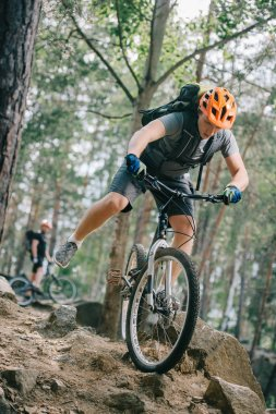 handsome young trial biker riding at beautiful forest