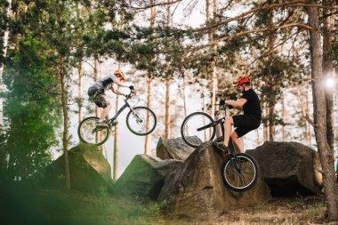 trial bikers performing stunts on rocks outdoors
