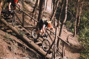 young trial bikers riding down stairs in forest