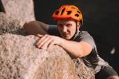 pohledný mladý cestovatelů v helmě lezení na skále a při pohledu na fotoaparát