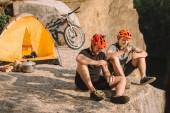 Happy zkušební motorkáři jíst konzervované potraviny v kempu na útesu