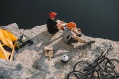 high angle view of active bike travellers eating canned food on rocky cliff over lake