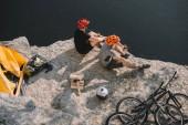vysoký úhel pohledu aktivní kola cestující jíst konzervované potraviny na skalnatém útesu nad jezerem