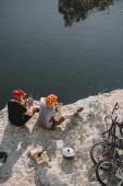Fotografie pohled z vysokého úhlu kolo cestujících jíst konzervované potraviny na skalnatém útesu nad jezerem