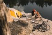 Fotografie pohled z vysokého úhlu aktivní zkušební motorkářů jíst konzervované potraviny v kempu na skalnatém útesu