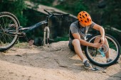 mladí zkušební biker stanovení jízdního kola venku, zatímco sedí na kameni