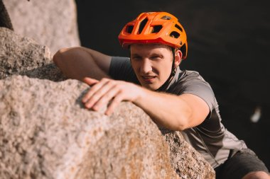 handsome young traveller in helmet climbing on rock and looking at camera