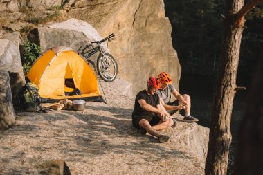 active young bike travellers with canned food sitting on cliff