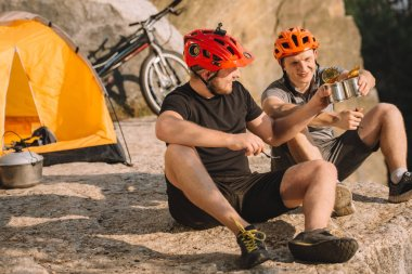 active travellers eating canned food on rocky cliff and clinking tins