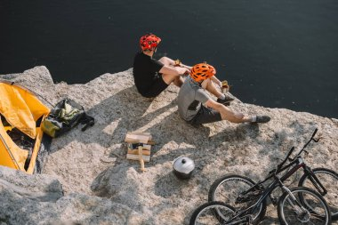 High angle view of active bike travellers eating canned food on rocky cliff over lake stock vector