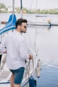 Fotografia giovane bello in occhiali da sole distoglie lo sguardo mentre si tiene la corda presso yacht